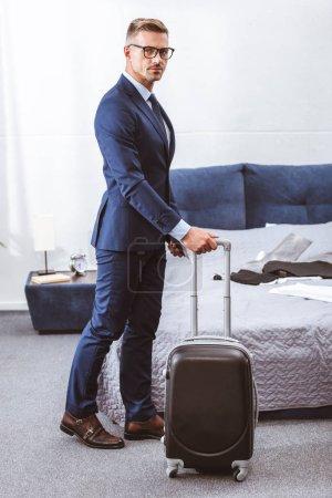 Photo pour Homme d'affaires en costume et lunettes tenant une valise et regardant la caméra dans la chambre - image libre de droit