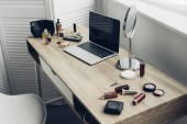 close-up shot of workplace with laptop and makeup supplies at home