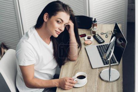 Photo pour Vue grand angle homme freelancer jeune transgenre avec tasse de café, assis au milieu de travail à la maison et regarder la caméra - image libre de droit