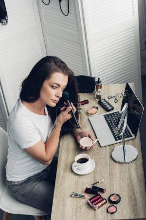 Foto de Hombre joven transexual haciendo maquillaje en el lugar de trabajo en casa - Imagen libre de derechos