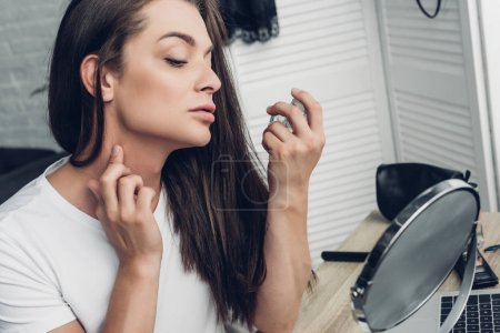 young transgender man applying perfume on neck at home