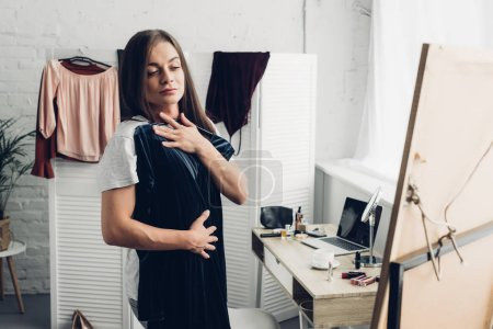 transgender man trying on dress and looking at mirror at home