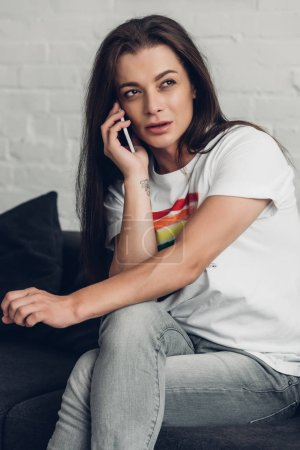 young transgender man talking by phone on couch at home