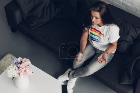 high angle view of young transgender man with pill and glass of water sitting on couch