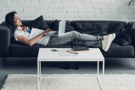 relaxed young transgender freelancer man working with laptop on couch at home
