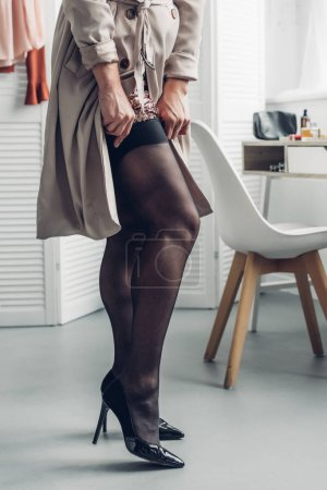 cropped shot of trans man in trench coat putting on stockings at home