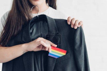 Photo pour Photo recadrée de transgenre homme prenant la carte avec le drapeau de la fierté hors de l'entreprise fonction de poche - image libre de droit