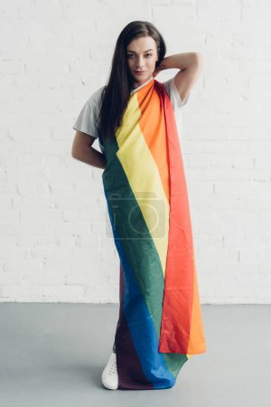 attractive young transgender man covering with pride flag and looking at camera in front of white brick wall