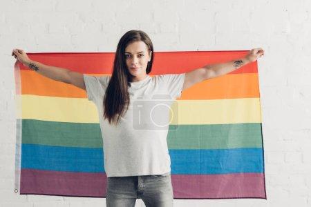 Photo pour Confiant transgenre homme tenant le drapeau de la fierté devant le mur de briques blanches - image libre de droit