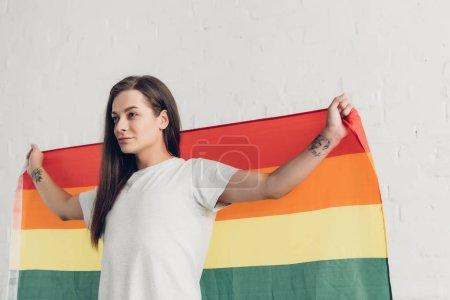 Photo pour Transgenre homme tenant le drapeau de la fierté devant le mur de briques blanches - image libre de droit