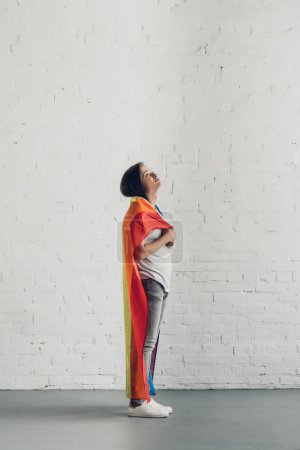young transgender man covering shoulders with pride flag in front of white brick wall