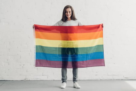 young transgender man holding pride flag in front of white brick wall