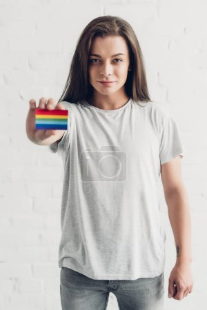 young transgender man holding card with pride flag in front of white brick wall
