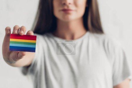 Photo pour Gros plan de jeune transgenre homme tenant la carte avec le drapeau de la fierté sur blanc - image libre de droit