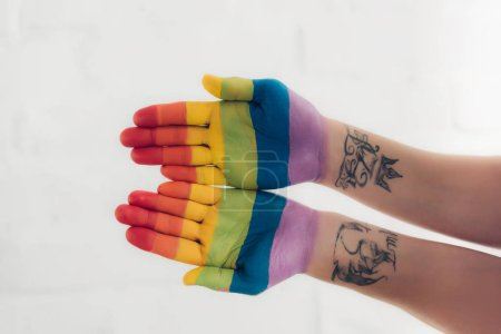 cropped shot of hands painted in colors of pride flag in front of white brick wall