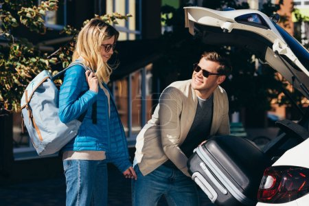 Photo for Man putting baggage into car with smiling girlfriend near by - Royalty Free Image
