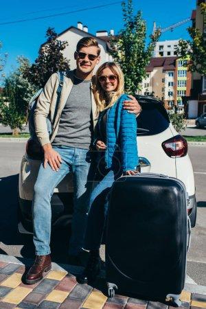 Photo pour Couple de touristes souriants avec bagages près de voiture sur la rue - image libre de droit