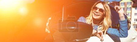 Photo pour Joyeuse jeune femme en lunettes de soleil penché voiture sur la rue - image libre de droit
