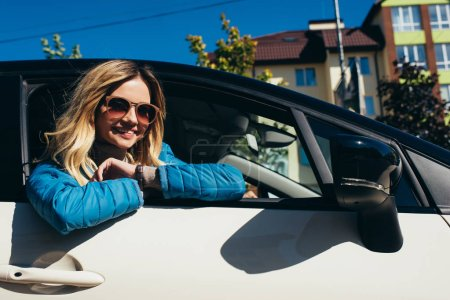 cheerful young woman in sunglasses leaning out car on street
