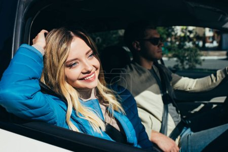 Photo for Smiling woman looking out car window while boyfriend driving car - Royalty Free Image