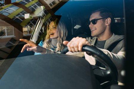 Photo pour Couple souriant de touristes conduisant la voiture tout en voyageant ensemble - image libre de droit
