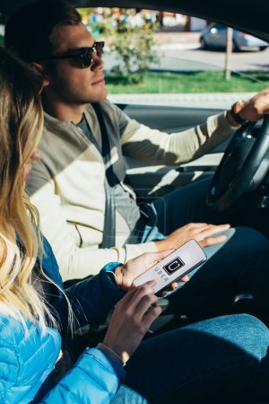 woman using smartphone with uber logo on screen while husband driving car