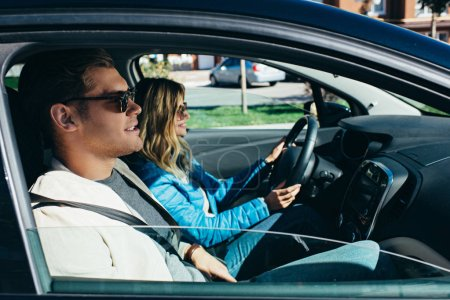 Photo for Side view of young woman driving car with boyfriend near by, traveling concept - Royalty Free Image