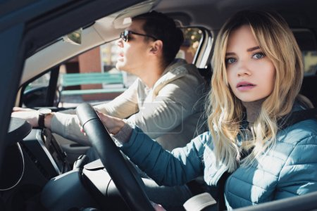 shocked woman at drivers seat looking at camera with boyfriend near by in car