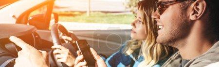 homme souriant avec smartphone indiquant la direction à amie cette voiture conduite