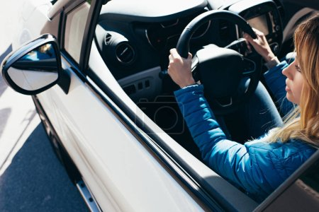 side view of young woman with hands on steering wheel driving car