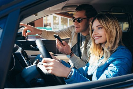 smiling man with smartphone showing direction to girlfriend that driving car