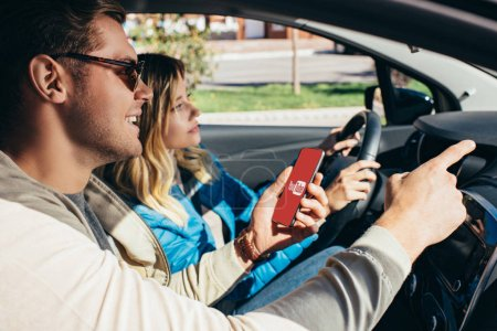 man with smartphone with youtube logo on screen showing direction to wife  in car