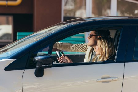 Photo for Side view of smiling woman driving car with boyfriend near by, traveling concept - Royalty Free Image