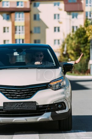 Photo for Young smiling man gesturing while driving car - Royalty Free Image