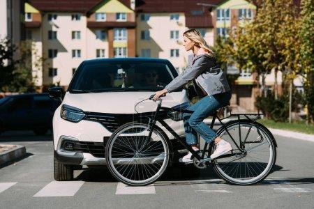 Photo pour Femme à vélo tout en traversant la route avec chauffeur en voiture - image libre de droit