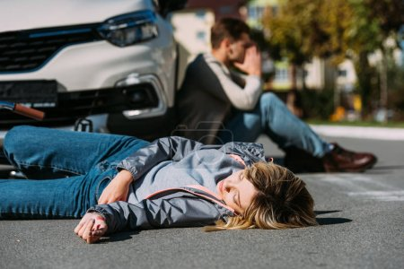 selective focus of injured woman lying on road after car accident with shocked car driver behind