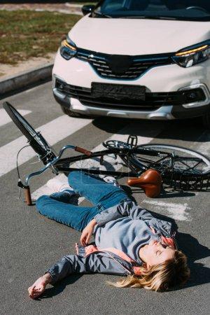 Photo pour Jeune femme aller fauché vers le bas en voiture pendant que vous conduisez le vélo sur route, concept d'accident de voiture - image libre de droit