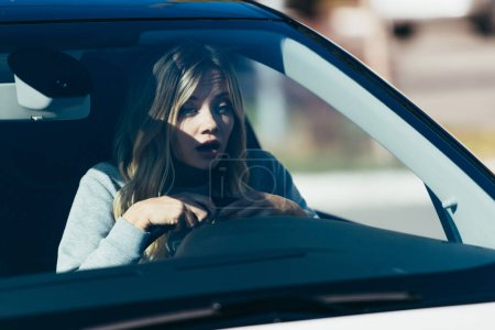 portrait of shocked woman looking on road while driving car