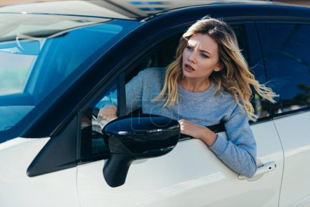 Photo for Young shocked woman leaning out car window while driving car - Royalty Free Image
