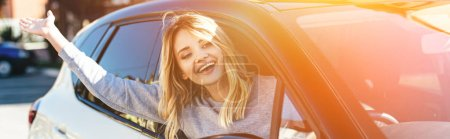 Photo for Portrait of happy blond woman waving to someone while driving car - Royalty Free Image
