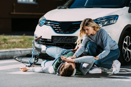 young woman trying to help injured cyclist at car accident