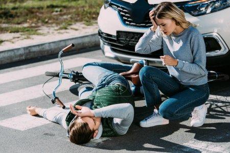 Photo pour Choqué de jeune femme regardant cycliste blessé se trouvant à vélo à l'accident de voiture - image libre de droit