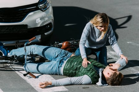 woman looking at injured young cyclist lying with bicycle on road at car accident