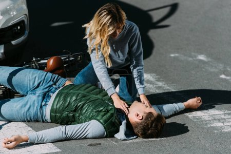 young woman checking pulse of injured cyclist after traffic collision