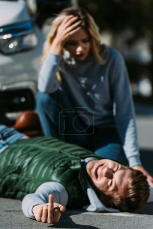 injured young man lying on road and showing middle finger after traffic collision