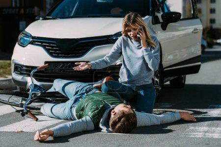 Photo pour Femme appel d'urgence et en regardant blessé cycliste couché sur la route après collision du trafic - image libre de droit
