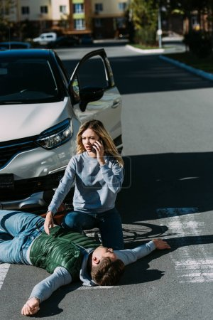 high angle view of young woman calling emergency white injured cyclist lying on road after car accident