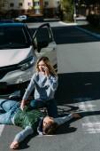 """Постер, картина, фотообои """"высокий угол зрения молодой женщины, вызов чрезвычайной белый травмы велосипедиста, лежащим на дороге после автомобильной аварии"""""""