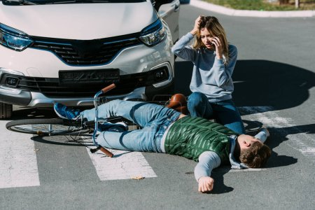 young woman calling emergency and looking at injured cyclist lying on road after car accident