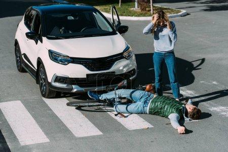 Photo pour Vue d'angle élevé de femme debout près de cycliste blessé après l'accident de voiture - image libre de droit